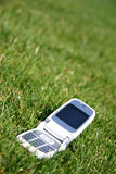 Mobile cell phone on grass outside. Mobile cell phone on green grass outside Royalty Free Stock Photography