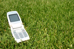 Mobile cell phone on grass outside. Mobile cell phone on green grass outside Stock Images