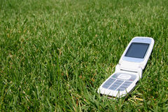 Mobile cell phone on grass outside. Open mobile cell phone on green grass outside Stock Images