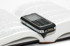 Mobile cellular phone. Over the study book Stock Images