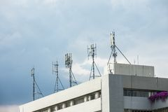 Mobile cellular telecommunication antenna network. On the building block with blue sky scene.Digital audio and video transmission Stock Images