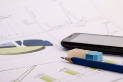 Mobile with chart. Charts with mobile, pen and rubber Stock Image
