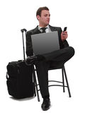 Mobile communication. Young businessman reading a phone message while she is sitting with his laptop next to her suitcase,isolated against a white background Stock Photo
