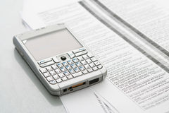 Mobile computer (organizer). On the documents at office table Royalty Free Stock Images