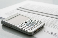Mobile computer (organizer). On the documents at office table Royalty Free Stock Image