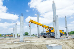 Mobile crane beam is among the concrete skeleton against blue cl Stock Photos