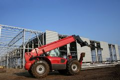 Mobile crane on building site. Side view of modern red mobile crane on construction site with blue sky background and copy space royalty free stock images