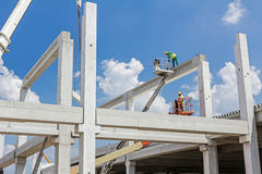 Mobile crane is carry concrete joist to assembly huge hall. Royalty Free Stock Photography