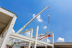 Mobile crane is carry concrete joist to assembly huge hall. Mobile crane is operating and worker is assembly concrete joist in high place. Height worker is Royalty Free Stock Image