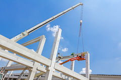 Mobile crane is carry concrete joist to assembly huge hall. Mobile crane is operating and worker is assembly concrete joist in high place. Height worker is Stock Image