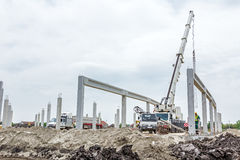Mobile crane is carry concrete joist to assembly huge hall. Zrenjanin, Vojvodina, Serbia - May 21, 2015: Mobile crane is operating and worker is assembly Stock Photos