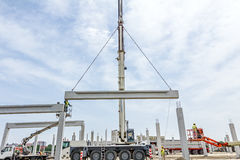 Mobile crane is carry concrete joist to assembly huge hall. Zrenjanin, Vojvodina, Serbia - May 21, 2015: Mobile crane is operating and worker is assembly Royalty Free Stock Photography
