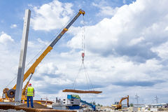 Mobile crane is carry pile of concrete armature, rusty square re Stock Photos