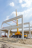 Mobile crane is operating and lifting concrete joist. Landscape. Mobile crane is carry concrete joist to assembly huge hall. Landscape transform into urban area Stock Image