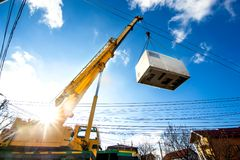 Mobile crane operating by lifting an electric generator. Mobile crane operating by lifting and moving an heavy electric generator Royalty Free Stock Photo