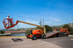 Mobile Crane Operator Flat Bed Truck. Mobile Crane Hoist machine controlled by operator from hydraulic extending arm off flat bed truck Stock Photography