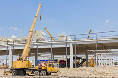 Mobile crane is raising package of glass wool on the roof huge u Stock Image