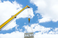 Mobile crane is raising package of glass wool on the roof huge u Royalty Free Stock Photo