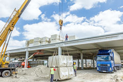 Mobile crane is raising package of glass wool on the roof huge u Stock Photography