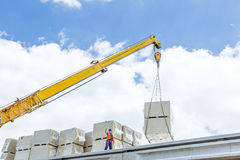 Mobile crane is raising package of glass wool on the roof huge u Royalty Free Stock Photos