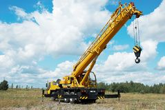 Mobile crane with risen boom. Yellow automobile crane with rised telescopic boom outdoors over blue sky Stock Photos