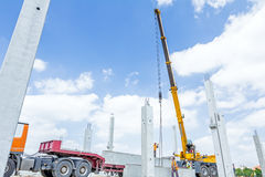 Mobile crane is unloading concrete joist from truck trailer. Mobile crane is carry concrete joist for assembly huge construction Royalty Free Stock Image