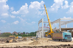 Mobile crane is unloading concrete joist from truck trailer. Mobile crane is carry concrete joist to assembly huge hall Royalty Free Stock Photos