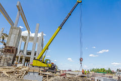 Mobile crane is unloading concrete joist from truck trailer. Mobile crane is working to assembly huge hall. Placing the truss on building skeleton Stock Image