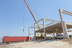 Mobile crane is unloading concrete joist from truck trailer. Stock Photography