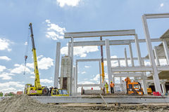 Mobile crane is unloading concrete joist from truck trailer. Zrenjanin, Vojvodina, Serbia - June 22, 2015: Mobile crane is working to assembly huge hall. Placing Royalty Free Stock Images