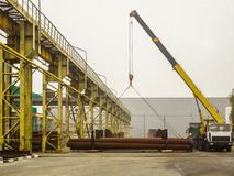 Mobile crane unloads steel pipes