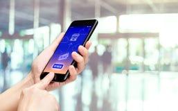 Mobile de participation de main avec la configuration de mot de salaire et d'icône de facture avec le fond de compteur de bureau  photos stock