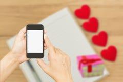 Mobile de prise de main au-dessus de coeur rouge Photographie stock libre de droits