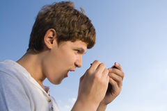 Mobile delight. Teenager with telephone in hand on sky background Stock Photography