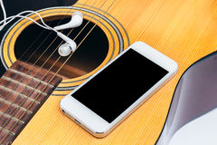 Mobile and earphone on guitar,selective focus Royalty Free Stock Photos