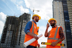 Mobile engineers. Contractor speaking on walkie-talkie with co-worker near by Royalty Free Stock Images