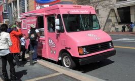 Food Truck. Mobile Food Truck, A popular pink cupcake van seen daily on street in Washington DC, and people are lining up to buy cup cakes and other foods royalty free stock photos