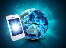 Mobile in front of earth on abstract background Royalty Free Stock Images