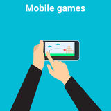 Mobile gaming. Young man is playing videogame on mobile phone app Royalty Free Stock Photos