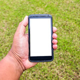 Mobile on hand with green grass Royalty Free Stock Photos