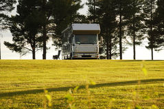 Mobile home on camping site into the sunset. Royalty Free Stock Photos