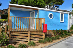 Mobile home in a campsite. A nice blue mobile home with a wooden veranda in a campsite royalty free stock photography