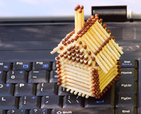 The mobile house. The match small house standing on the keyboard of the laptop Royalty Free Stock Images