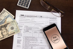 Mobile income tax filing. Mobile tax filing - 1040 forms with cell phone and calculator Stock Photography