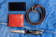Mobile, a knife, a belt, a wallet. On the background of denim Royalty Free Stock Images