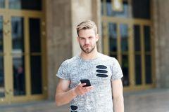 Mobile lifestyle. Caucasian guy using mobile phone outdoor. Handsome man with personal mobile device in hand on city. Street. Stylish man enjoying mobile stock photos