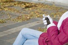 Mobile mit Kopfhörern in den Händen des Mädchens Lizenzfreie Stockfotos
