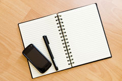 Mobile and Notebook. On Wooden Table Stock Photography