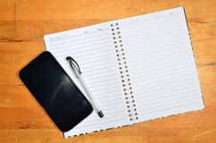 Mobile and Notebook on Wooden Table Stock Photos