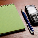 Mobile  on the notepad composition Royalty Free Stock Photo